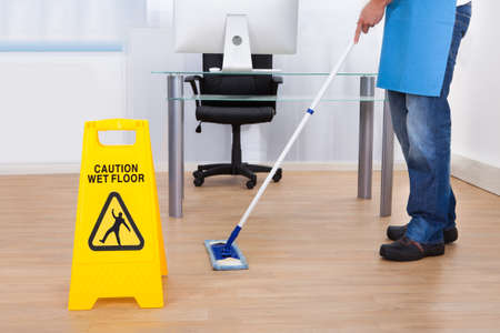 Yellow warning notice to caution people to a slippery wet surface as a janitor mops the floor in an office building
