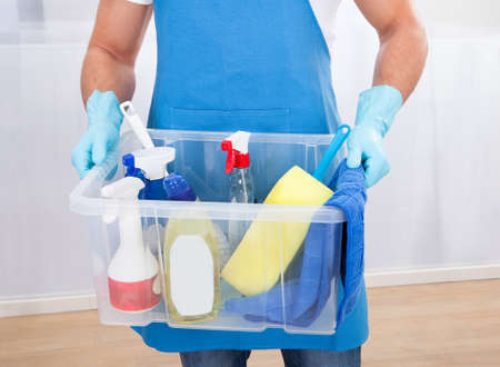 Janitor or cleaner wearing an apron and gloves carrying a tub of cleaning supplies as he goes about his work at the office