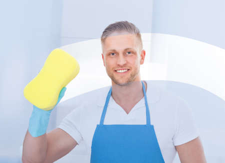 Male janitor using a sponge to clean a window in an office wearing an apron and gloves as he works