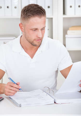 concentrates: Businessman working at his desk in the office sitting writing notes in a short-sleeved white shirt