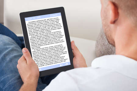 man holding book: Man relaxing at home reading an e-book online or studying long distance on his tablet
