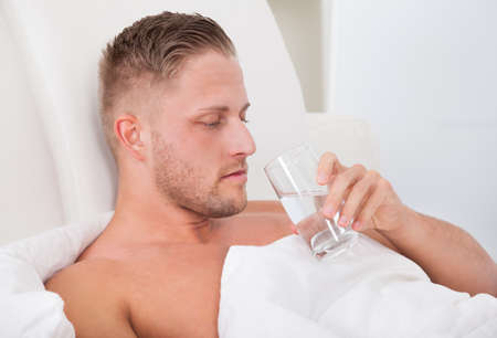recuperating: Man lying in bed propped up against the pillows drinking a glass of fresh water