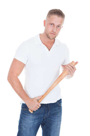 Bully or thug standing holding a baseball bat in his hands and looking at the camera with a menacing stare and threatening attitude  isolated on white photo