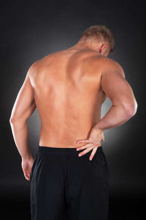 lower body: View from behind of a shirtless strong muscular man with backache clutching his lower back with his hand