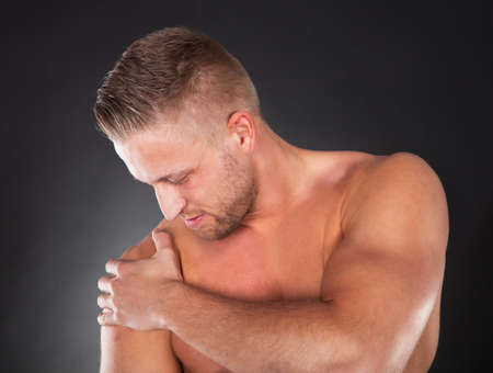arm pain: Muscular shirtless sportsman massaging his shoulder following a sprain or muscle injury looking down with a serious expression Stock Photo