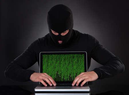 violación: Hacker de pie en un pasamontañas en la oscuridad robar furtivamente los datos de una computadora portátil o de la inserción de spyware en una seguridad en línea y el concepto de riesgo Foto de archivo