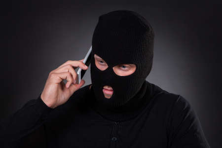balaclava: Thief in a balaclava and black outfit standing in the darkness using a stolen mobile phone or a terrorist activating a bomb remotely