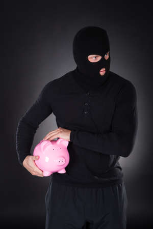 furtive: Furtive thief or burglar wearing a black outfit and balaclava making his escape through darkness stealing a pink piggy bank conceptual of theft of savings and investments