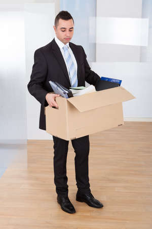 Full length of sad young businessman moving out with cardboard box from office photo