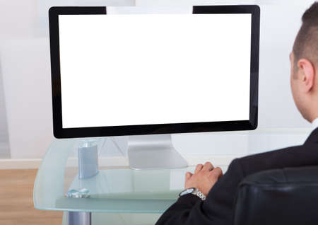Rear view of young businessman using computer at office desk photo