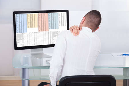 Rear view of young businessman with shoulder pain using computer at office desk photo