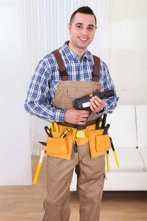 Full length portrait of confident male repairman holding drill machine in living room