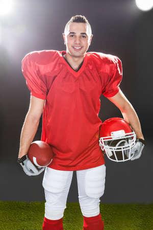 Retrato de cuerpo entero de la sonrisa del jugador de fútbol americano que se coloca en el campo en la noche Foto de archivo - 27002322