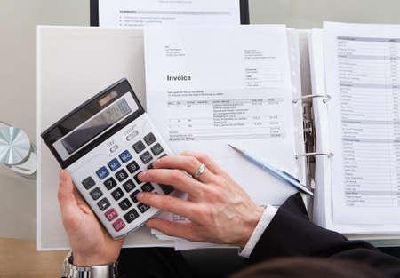 calculadora: Recorta la imagen de hombre de negocios c�lculo de la factura en el escritorio en la oficina Foto de archivo