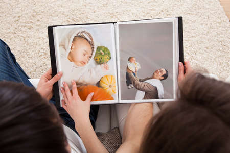 family memories: Portrait Of Couple Looking At Photo Album