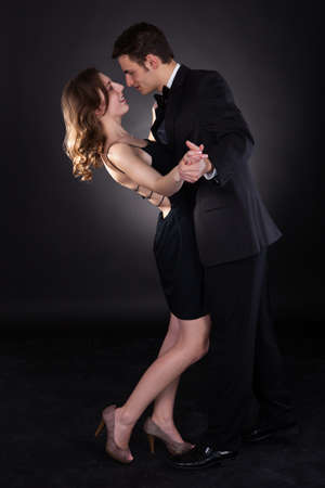 Full length of an elegant couple dancing together isolated over black background photo
