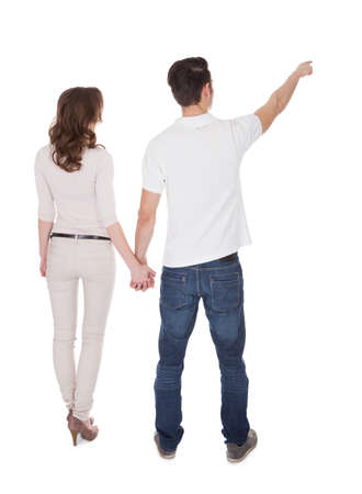 lovers holding hands: Full length rear view of young man pointing while holding womans hand isolated over white background