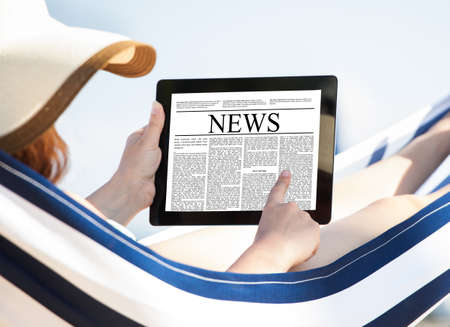 Woman reading newspaper on digital tablet while relaxing in hammock at beach
