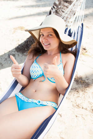 High angle view of young woman gesturing thumbs up in hammock at beach photo