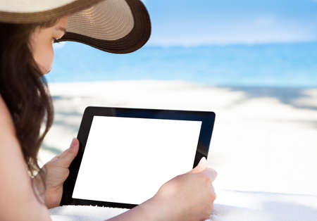 Cropped image woman holding digital tablet with blank screen at beach photo