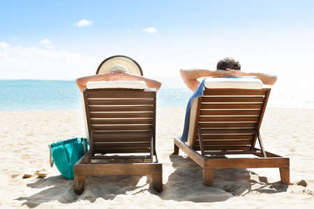 sea resort: Rear view of couple relaxing on deck chairs at beach resort Stock Photo