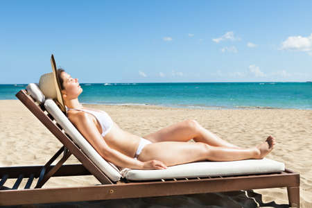 deck chair: Side view of young woman in bikini sunbathing on deck chair at beach