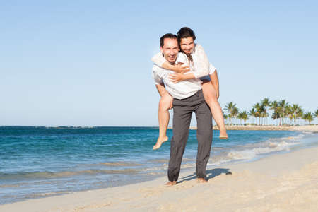piggyback ride: Full length portrait of loving man giving piggyback ride to woman at beach Stock Photo