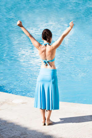 Full length rear view of woman with arms raised standing at poolside photo