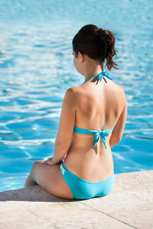 Rear view of woman sitting at the edge of swimming pool photo