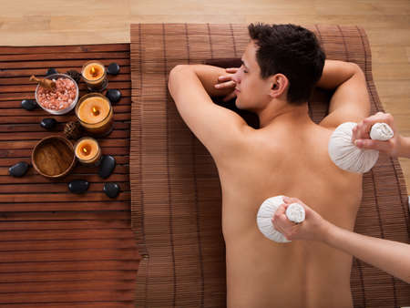 High angle view of young man receiving massage with stamps in spa photo
