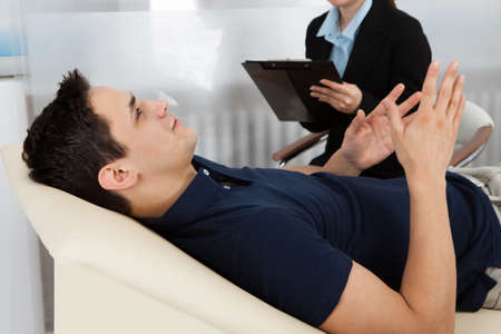couches: Female psychologist writing notes while patient lying on bed in clinic Stock Photo