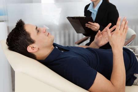 psicologia: Psicólogo Mujer escribiendo notas mientras el paciente acostado en la cama en la clínica