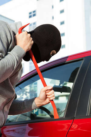 Thief in hooded jacket and balaclava opening cars door with crowbar