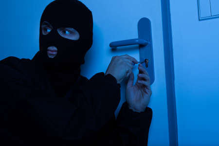 trespass: Thief in balaclava opening house door with tool