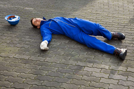 Full length of young unconscious repairman in uniform lying on street photo