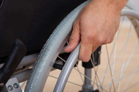 paralysis: Closeup of handicapped mans hand pushing wheel of wheelchair