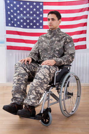 Full length of patriotic soldier sitting on wheel chair against American flag photo