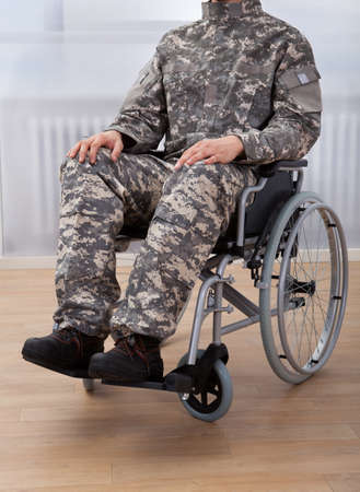 Cropped image of patriotic soldier sitting on wheel chair at home photo
