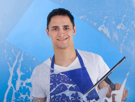 squeegee: Portrait of young male servant cleaning glass with squeegee over blue background