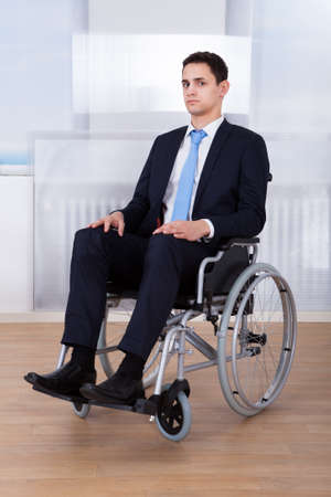 Portrait of confident disabled businessman sitting on wheelchair in office photo