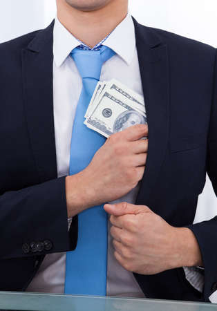 bribe: Midsection of businessman putting bribe money in suit pocket