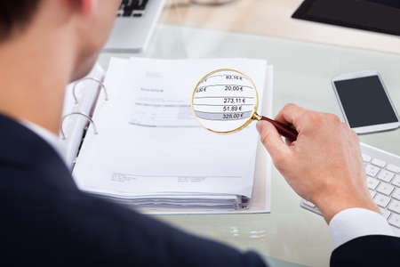 cropped image: Cropped image of auditor examining invoice with magnifying glass at desk