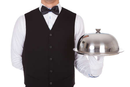 Midsection of waiter holding tray metal cloche lid cover against white background photo