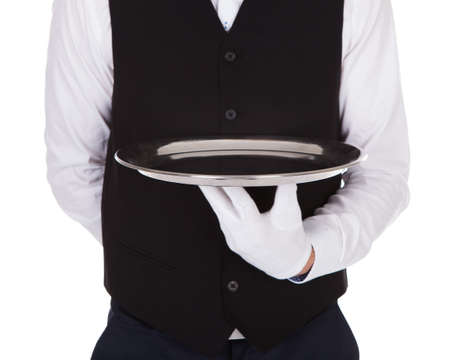 Midsection of waiter holding empty tray over white background photo