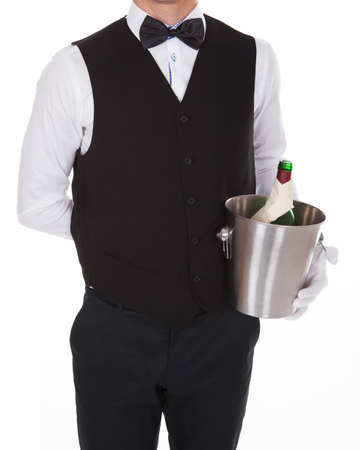 Cropped image of confident waiter holding champagne bottle in cooler over white background photo