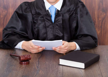 judge hammer: Midsection of judge holding documents while sitting at desk Stock Photo