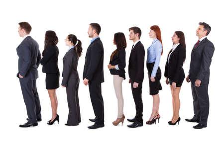 La gente de negocios de pie en la cola de más de fondo blanco