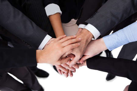 High angle close-up shot of business people stacking hands photo
