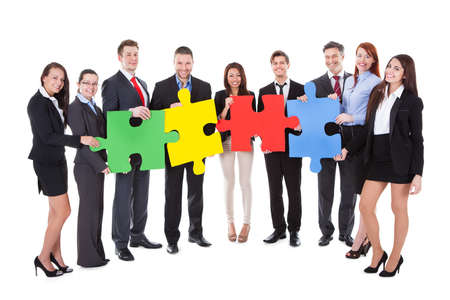Group of businesspeople holding four large brightly colored puzzle pieces conceptual of teamwork in solving a business problem or meeting a challenge  isolated on white Stock Photo