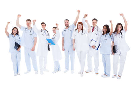 Large diverse multiethnic medical team standing cheering and punching the air with their fists as they celebrate a success or motivate themselves  isolated on white